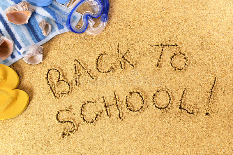 Terug naar schoolbericht op strandzand wordt geschreven, eind van het concept dat van de de zomervakantie stock foto