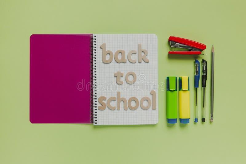 Terug naar schoolbrieven op een notitieboekje met andere materiaal en groene achtergrond stock afbeelding