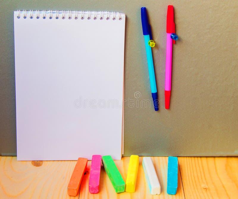 Terug naar schoolconcept, een pen, Blocnote, krijt stock afbeeldingen