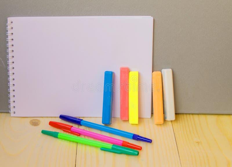 Terug naar schoolconcept, een pen, Blocnote, krijt stock afbeelding