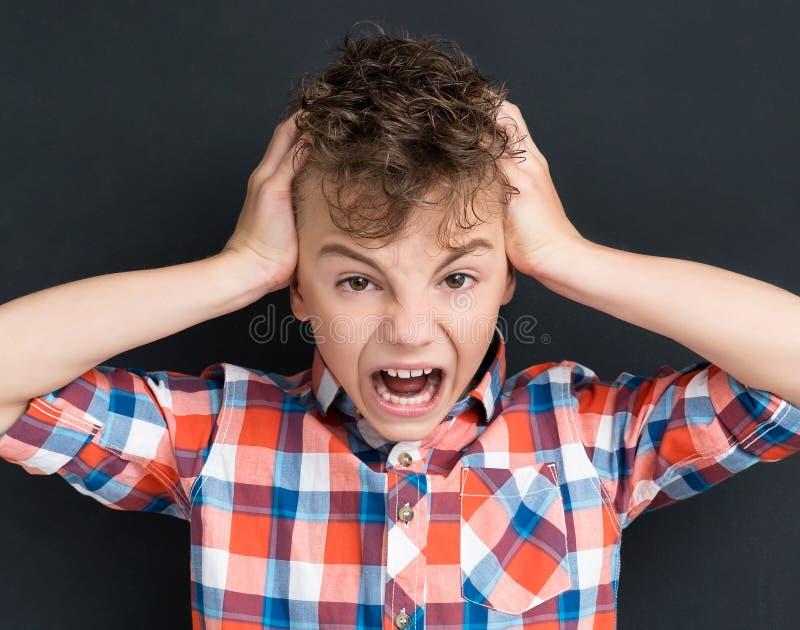 Terug naar schoolconcept - geschokte jonge jongen bij zwarte chalkboa stock foto's