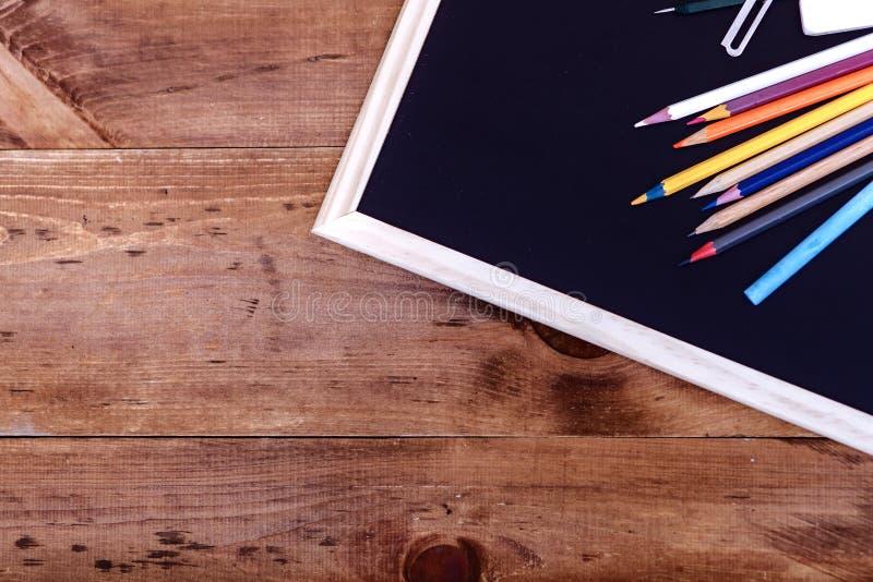 Terug naar schoolconcept, kleurpotloden op zwarte lijst, multicolored kantoorbehoeftentoebehoren voor het jonge geitje die van he royalty-vrije stock afbeelding