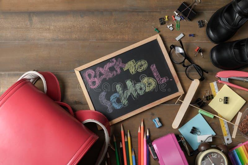 Terug naar schooltekst op zwart schoolbord met zak royalty-vrije stock foto
