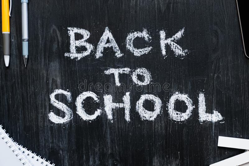 Terug naar Schooluitdrukking die op een zwarte houten achtergrond wordt geschreven royalty-vrije stock fotografie