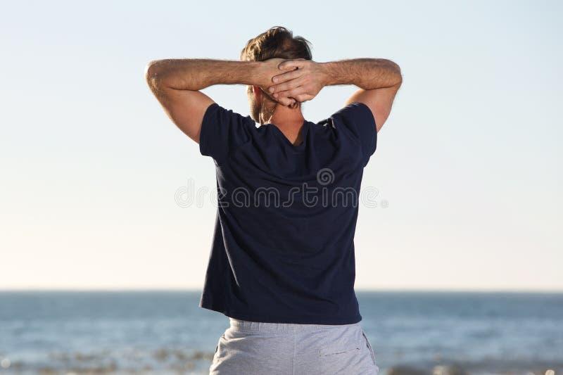 Terug van de mens die zich met handen achter hoofd bevinden die op zee kijken stock foto's