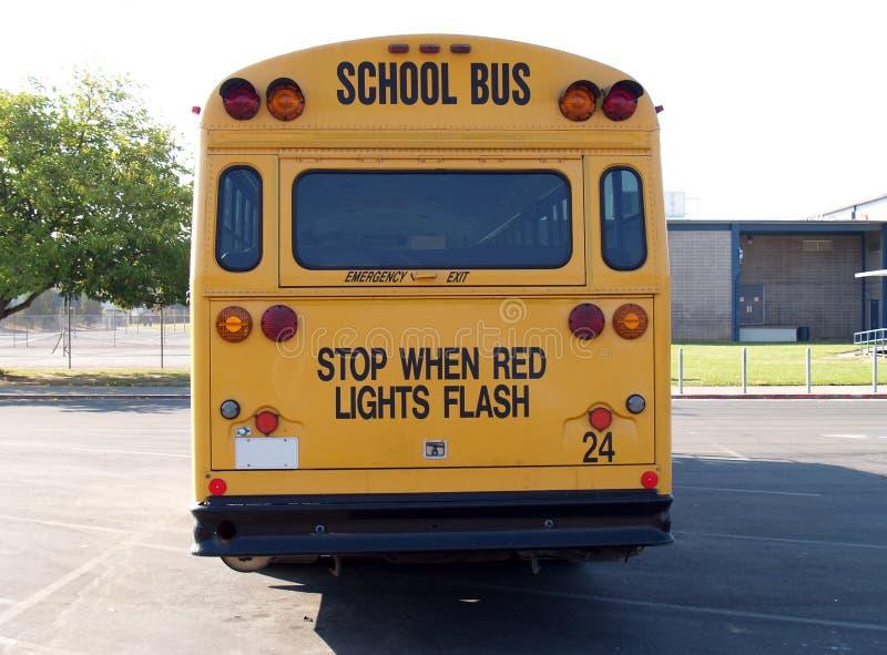 Terug van gele schoolbus in parkeerterrein stock afbeeldingen