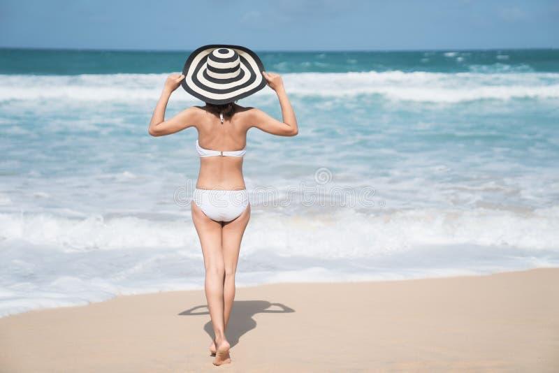 Terug van jonge vrouw in bikini die zich op het strand, Jonge mooie sexy vrouw in bikinizwempak bevinden, tropisch eiland, de zom royalty-vrije stock fotografie