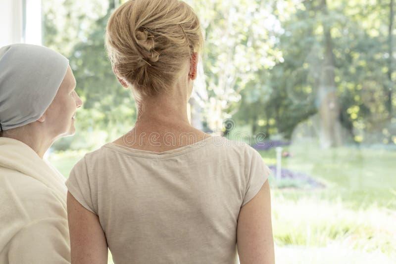 Terug van moeder met kanker en dochter het kijken door het venster stock foto