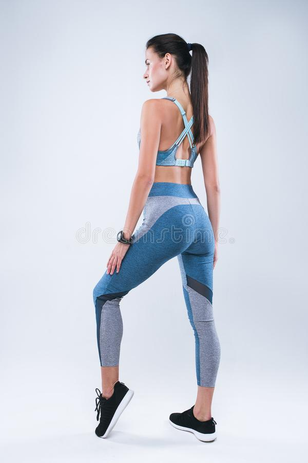 Terug van mooie geschiktheidsvrouw Fitness girl do sport oefeningen over grijze achtergrond stock fotografie
