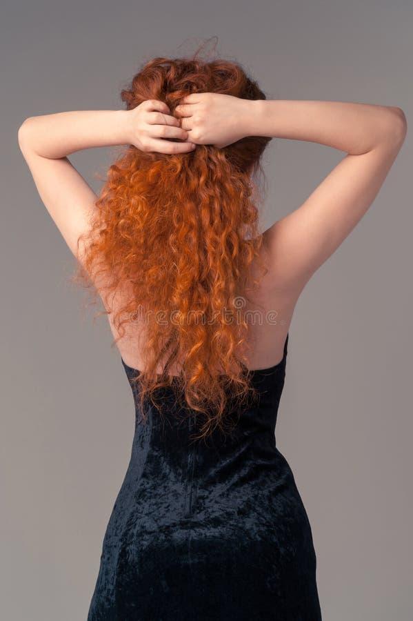 Terug van slanke vrouw. Jonge vrouwelijke aanraking haar haren royalty-vrije stock afbeeldingen