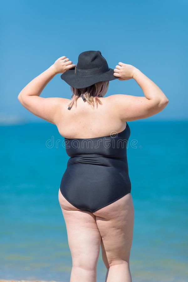Terug van te zware vrouw in zwart zwempak en zwarte hoed royalty-vrije stock afbeelding