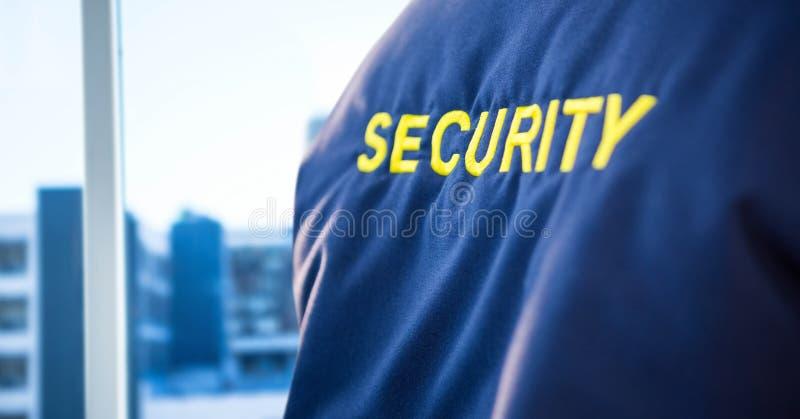 Terug van veiligheidsagentjasje tegen onscherp venster die stad tonen stock foto's