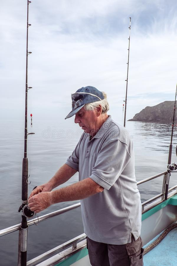 Teruggetrokken hogere mannelijke volwassen toerist op een visserijcharter boot bij M stock fotografie