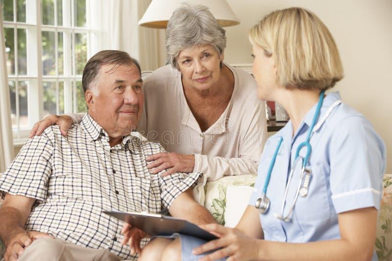 Teruggetrokken Hogere Mens die Gezondheidscontrole met Verpleegster At Home hebben stock afbeelding
