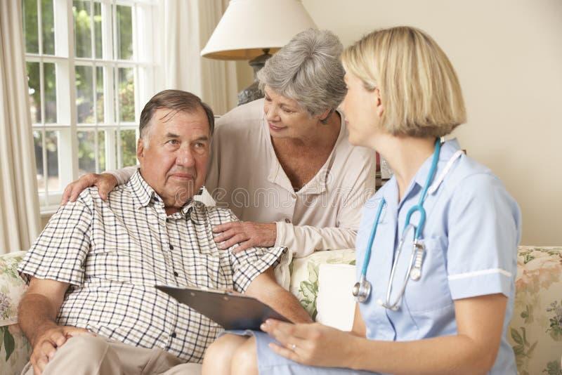 Teruggetrokken Hogere Mens die Gezondheidscontrole met Verpleegster At Home hebben stock fotografie