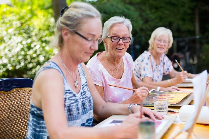 Teruggetrokken hogere vrouwen die samen in openlucht als groeps recreatieve en creatieve activiteit tijdens de zomer schilderen stock foto