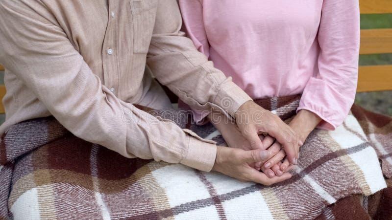 Teruggetrokken mens die vrouwenhanden, gepensioneerdepaar behandelen die samen in tuin rusten stock foto
