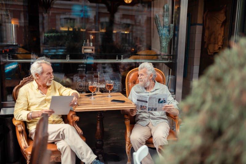 Teruggetrokken mensen die wisky drinken en ochtendnieuws lezen royalty-vrije stock afbeelding