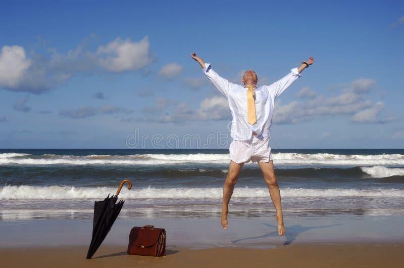 Teruggetrokken zakenman die met geluk op een mooi tropisch strand springen, het concept van de pensioneringsvrijheid stock foto's