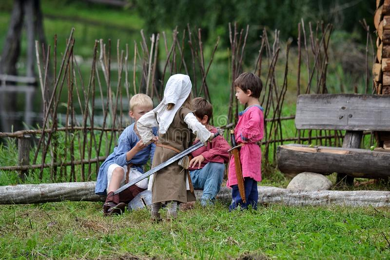TERVETE, LATVIA - AUGUST 13, 2011: Historical Zemgalu days. Unknown children in ancient clothing with ancient weapons into groups stock photography