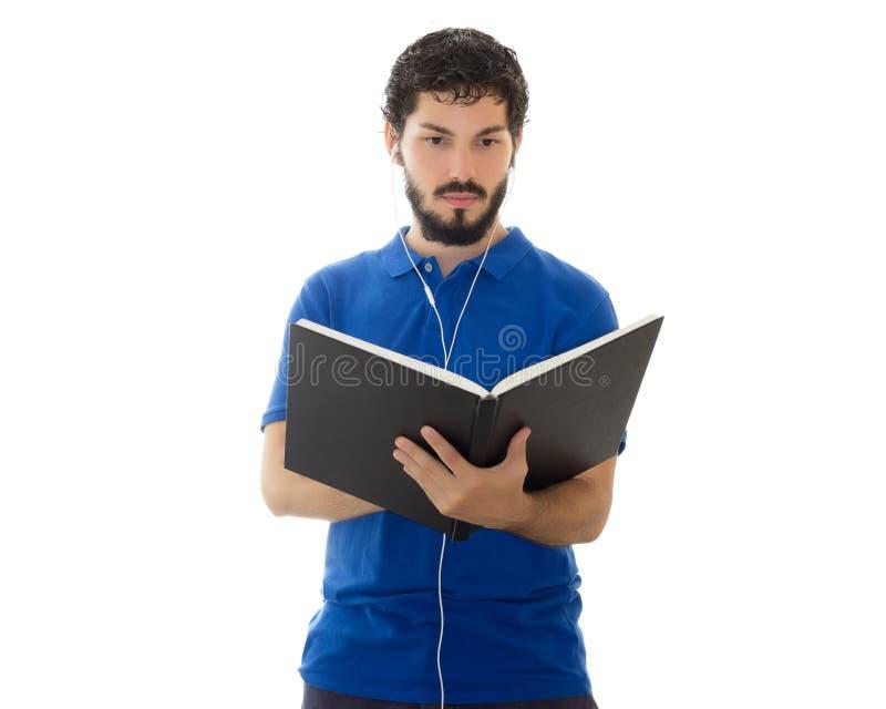 Terwijl het luisteren aan muziek leest het jonge mannetje een boek stock afbeelding