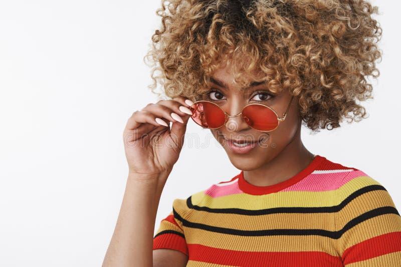 ?tes vous s?rieux Portrait de la femelle mignonne interrog?e et douteuse d'afro-am?ricain enlevant des lunettes de soleil et rega photographie stock