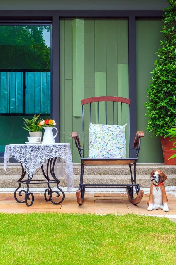 Teservis på tabellen och stolen i trädgården royaltyfri bild