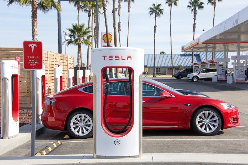 Tesla-Überverdichterstation in zentralem Kalifornien, Tankstelle im Hintergrund stockfoto