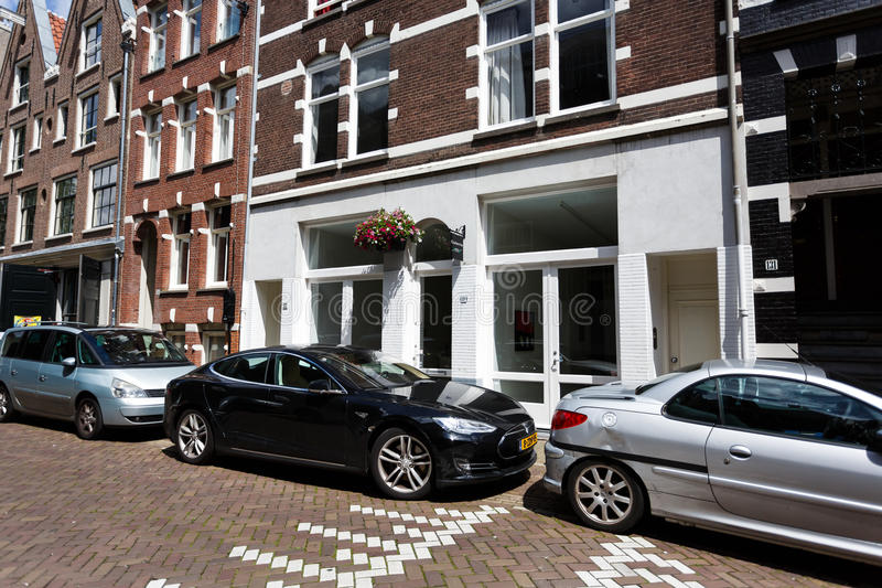 Tesla car on the street of Amsterdam. Amsterdam, Netherlands - July 03 2016: Tesla car parked on a street nearby the traditional Dutch houses royalty free stock photography