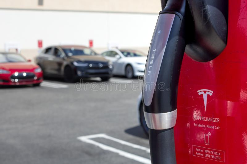 Tesla charging station pump and vehicles stock photo