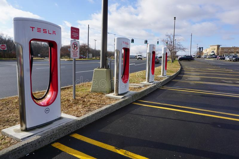 Tesla charging stations unveiled in Danbury. Four self charging ports stand available for electric vehicles to plug in. Sun shines on Brio restaurant and empty royalty free stock photos
