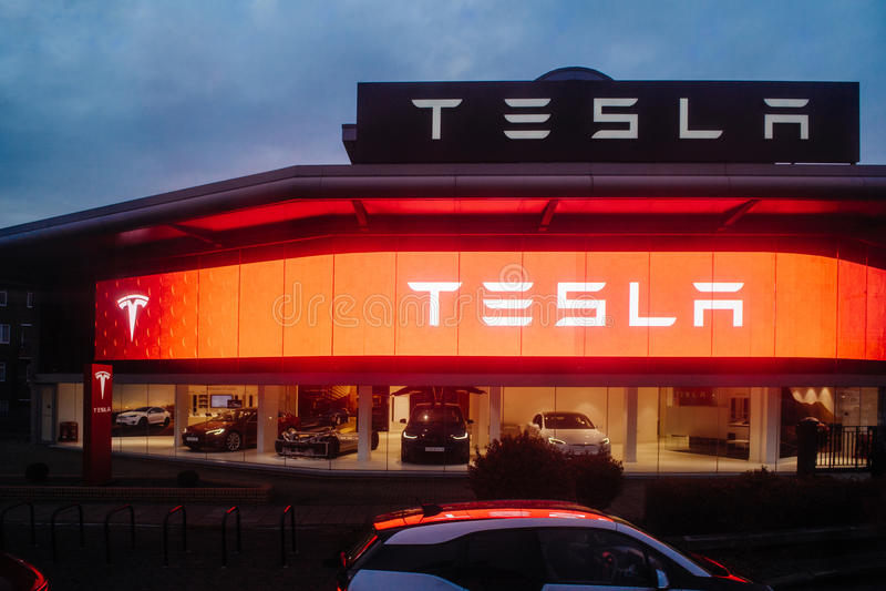 Tesla fährt Ausstellungsraum mit Autos innerhalb und belichteter Logokleie stockfoto