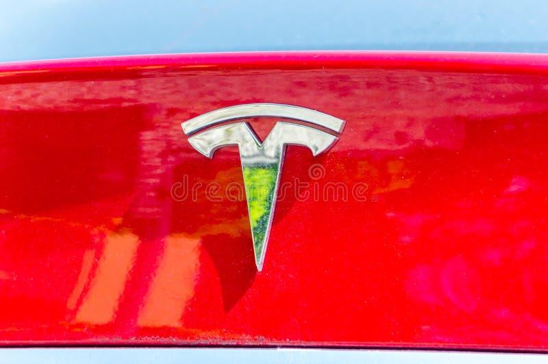 Tesla-Logo auf einer roten Fahrzeugkarosserie lizenzfreie stockbilder