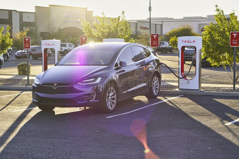 Tesla Model X charging at a Supercharger stock images