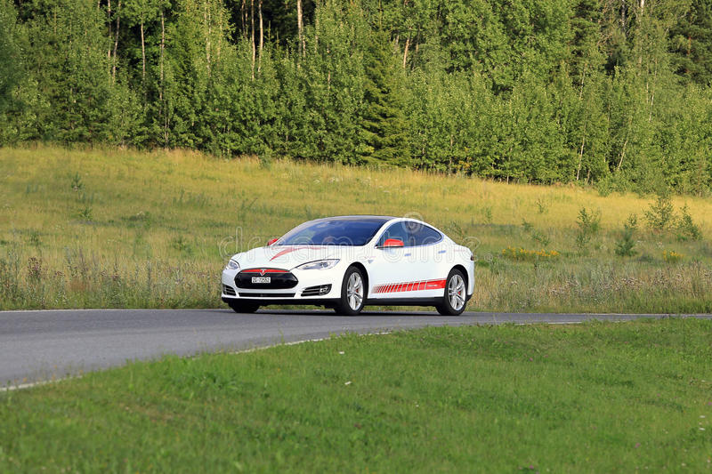 Tesla Model S Electric Car and Green Rural Road. PAIMIO, FINLAND - JULY 24, 2016: Tesla Model S unique design electric car drives along rural road in South of stock photos