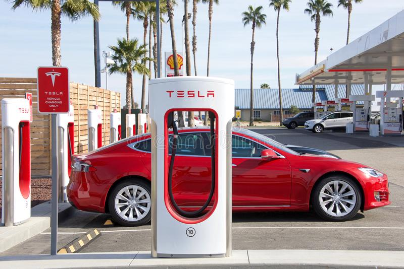 Tesla supercharger station in Central California, gas station in background stock photo
