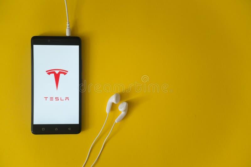 Teslaembleem op het smartphonescherm op gele achtergrond royalty-vrije stock foto