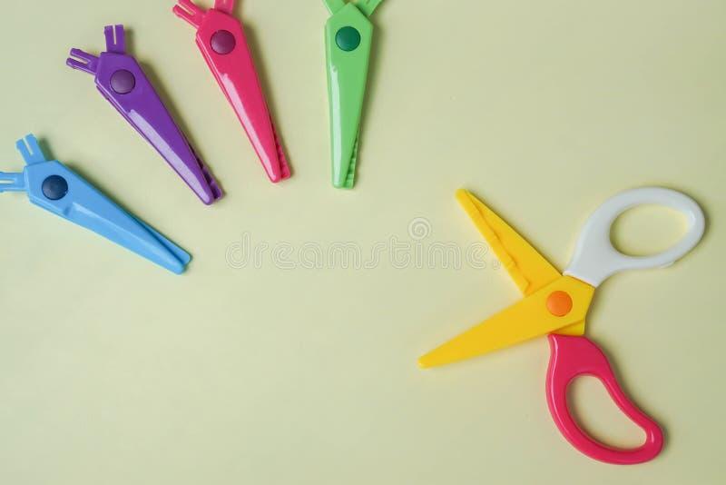 Tesouras com as lâminas do ziguezague em várias cores como ferramentas de corte com fundo amarelo foto de stock royalty free