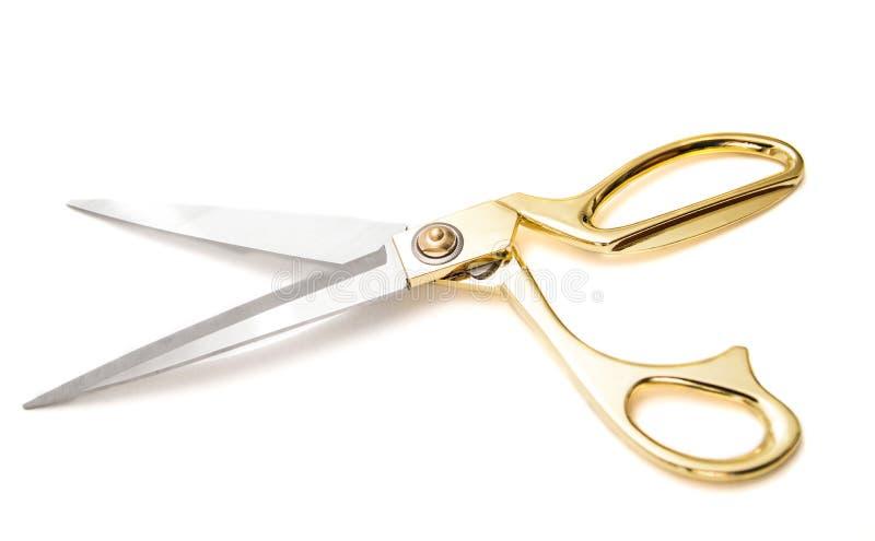 Tesouras douradas do metal para cortar a mentira em um fundo branco fotografia de stock royalty free