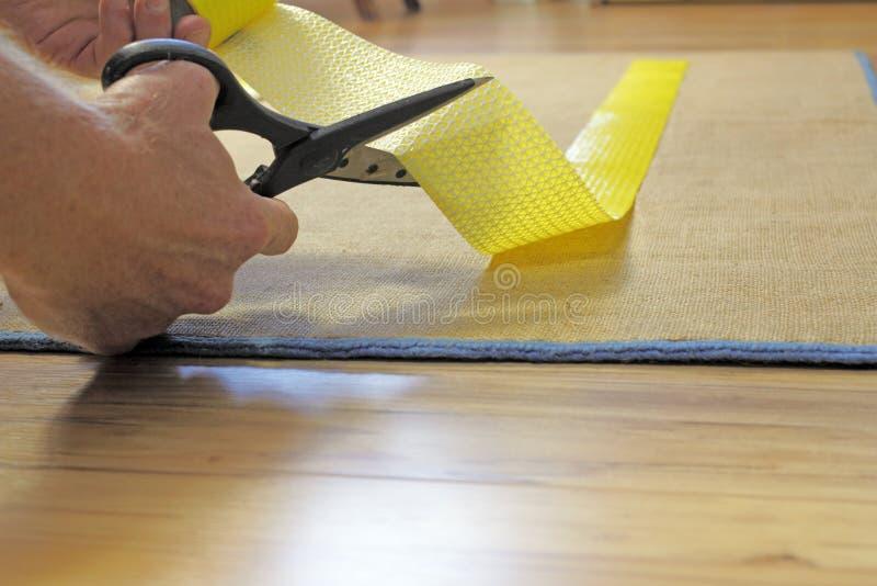 Tesouras que cortam a fita do aperto do tapete foto de stock