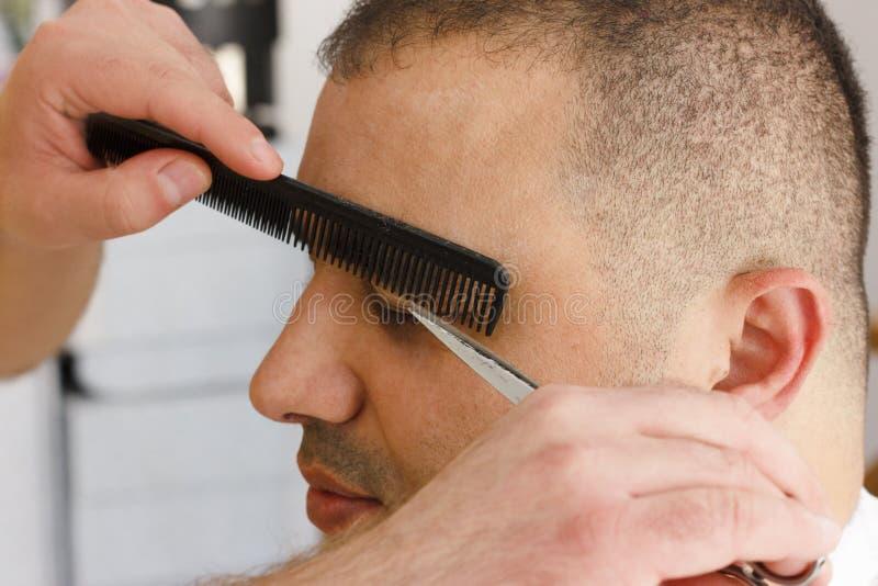 Tesouras que cortam a sobrancelha do homem no barbeiro Testa que prepara perto acima fotografia de stock