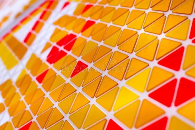 Tessellation av en nivå med orange och röd kulöra triaen den guling, royaltyfri bild