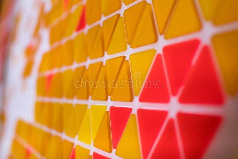 Tessellation av en nivå med orange och röd kulöra triaen den guling, arkivfoto