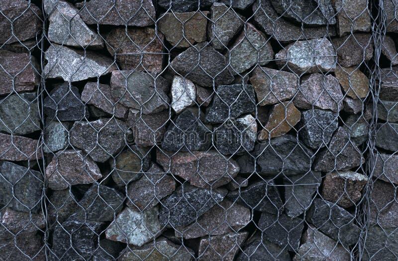 Tessitura di muratura, sfondo di pietra recintato con maglia di ferro immagine stock