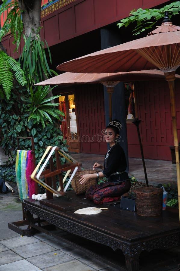 Tessitura di seta tailandese da una bella signora a Jim Thomson House, Bangkok fotografia stock libera da diritti