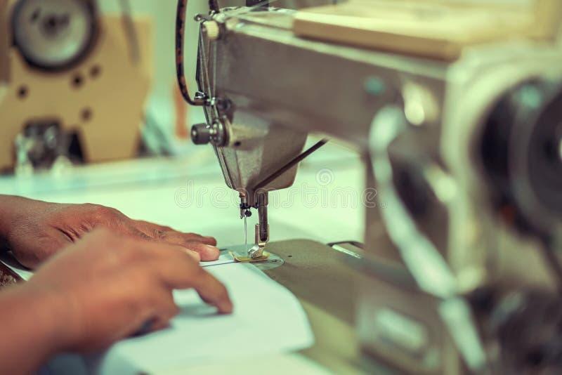 tessuto bianco di cucitura del lavoratore delle mani del primo piano sulla macchina per cucire fotografia stock libera da diritti