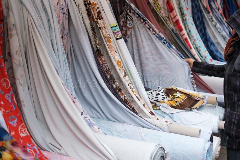 Tessuto di acquisto della donna, rotoli del tessuto e tessuti sul mercato immagini stock libere da diritti