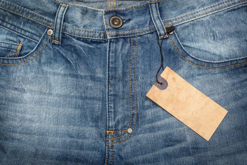 Tessuto - serie del tessuto: Jeans con l'etichetta in bianco immagini stock