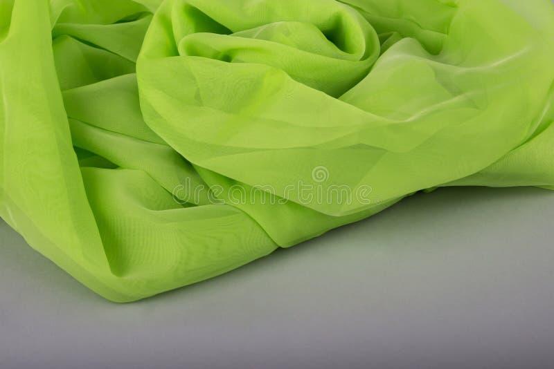 Tessuto verde su un fondo grigio Tessuto di seta tessuto verde sottile del fondo verde strutture di seta in raso o velluto Verde  fotografia stock