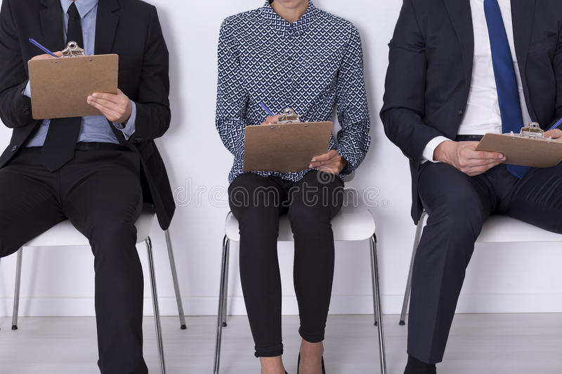 On this test depends their work. Three elegant people sitting in light interior writing qualification test stock images